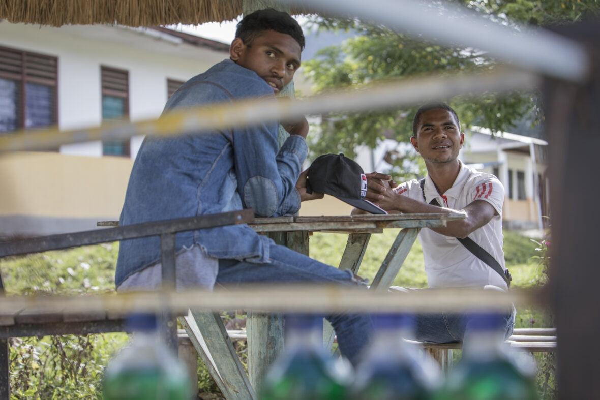 Kaksi nuorta itätimorilaista poikaa istuu pöydän ääressä koulun pihalla.