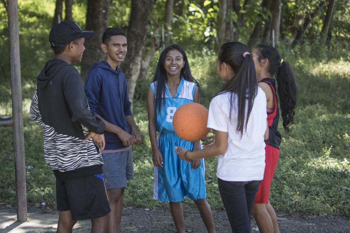 Joukko itätimorilaisnuoria koripallokentällä koripallo kädessä.