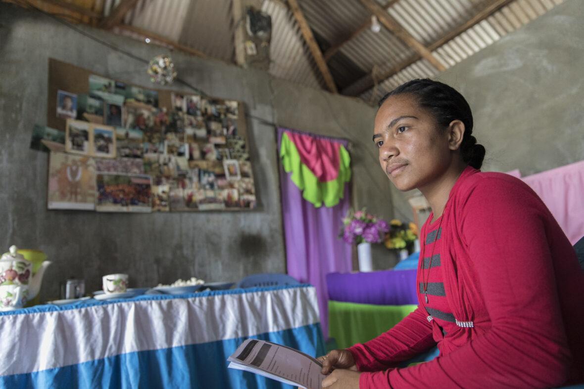 Itätimorilainen Francelina istuu kotonaan kirja kädessä.