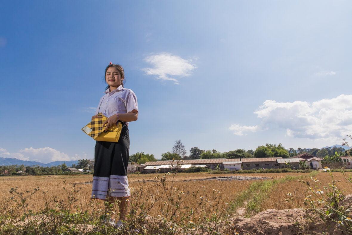 Laosilainen Jim kävelee koululaukku kädessään keskellä peltoa.