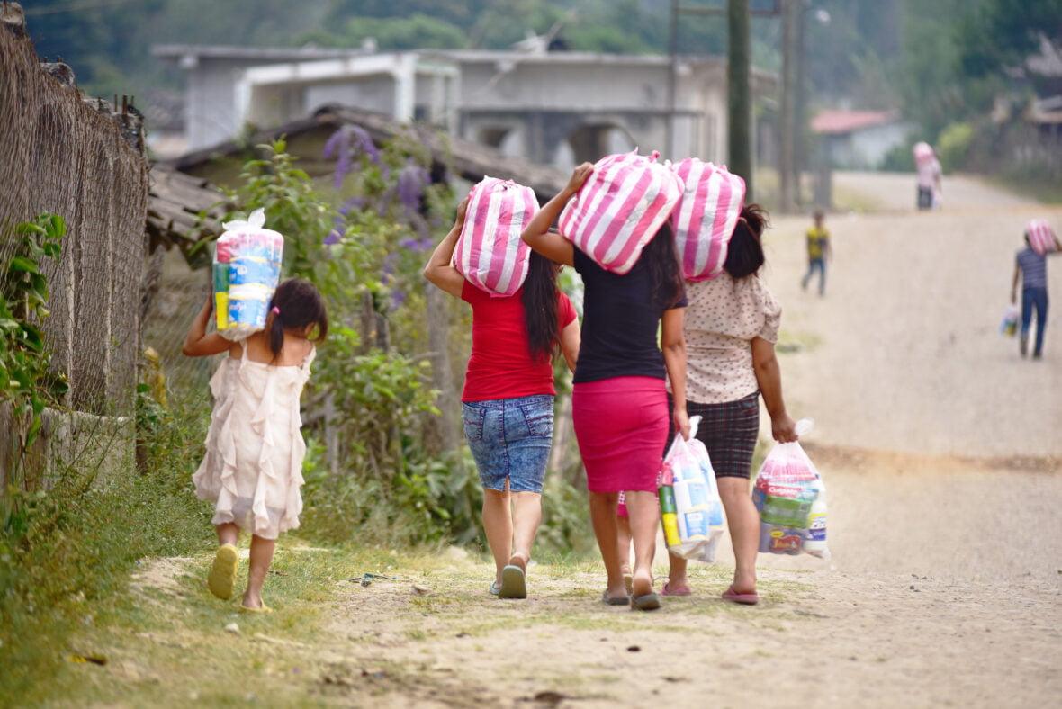 Hondurasilaisnaiset kävelevät poispäin kantaen isoja säkkejä. Kuvituskuva.