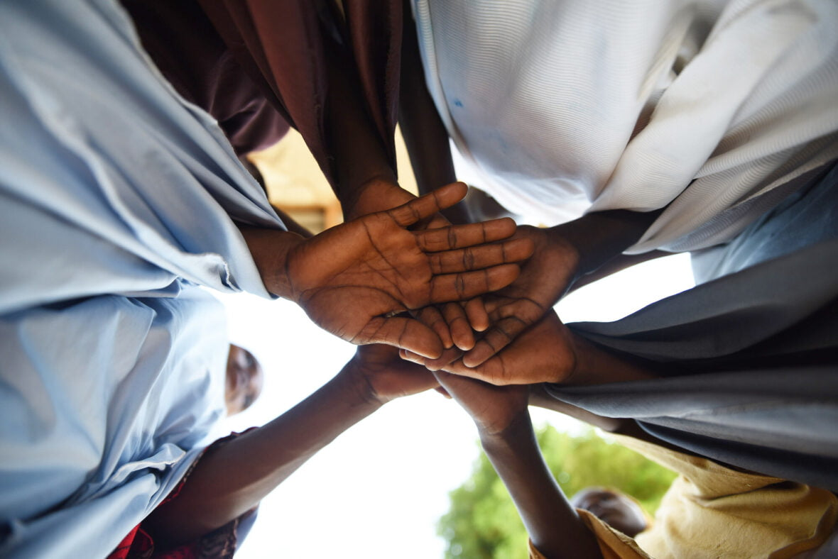 Nigerialaisnaisten käsiä yhdessä.