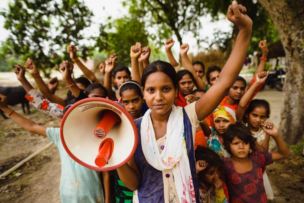 Intialainen Shalini pitelee megafonia kädessään kätensä ilmaan nostaneen tyttöryhmän edessä.