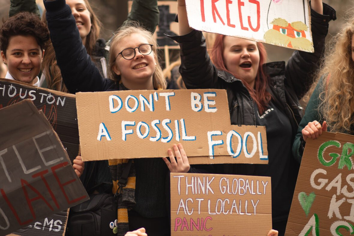 Nuoret pitelevät mielenosoituksessa kylttejä, joista yhdessä lukee don't be a fossil fool.