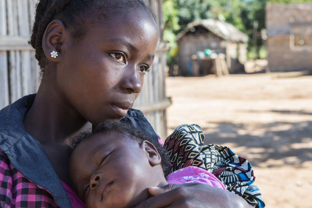 Mosambikilainen nuori nainen pitelee lasta sylissään vakava ilme kasvoillaan.