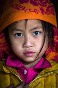 Vietnamilainen tyttö katsoo kameraan.
