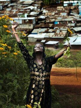 Kenialainen nuori nainen on nostanut kätensä ilmaan ja katsoo ylöspäin.