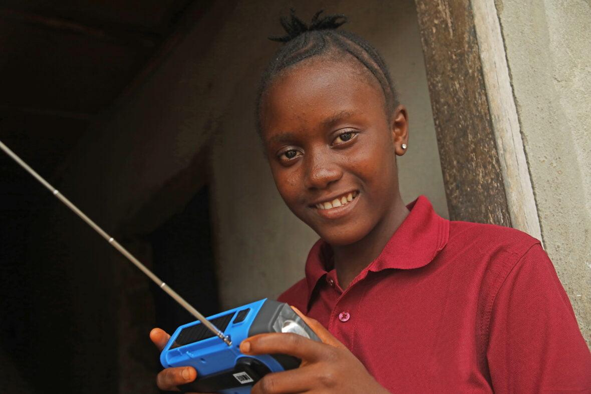 Sierraleonelainen tyttö pitelee sinistä radiota kädessään ja hymyilee.