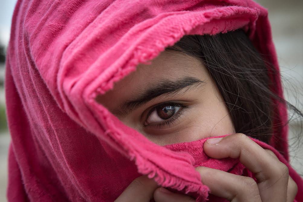 Nuori tyttö kurkistaa kasvojensa edessä olevan vaaleanpunaisen huivin takaa.