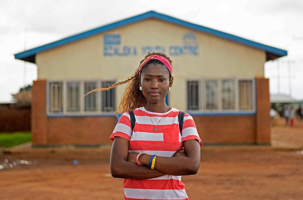 Tyttö seisoo pakolaisleirillä käset puuskassa ja katsoo vakavana kameraan.