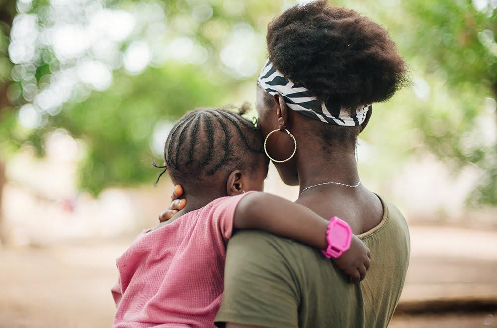 Tyttö seisoo selkä kameraan päin ja pitelee lasta sylissään olkapäätään vasten.