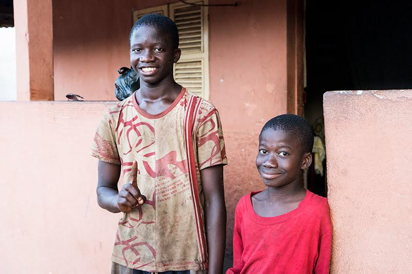 Kaksi poikaa seisoo talon portilla ja hymyilee.