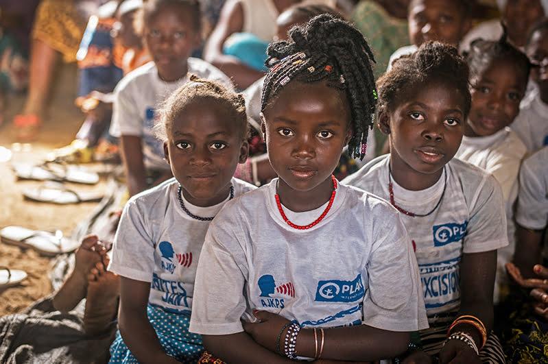 Ryhmä guinealaisia tyttöjä istuu lattialla ja katsoo kohti kameraa.