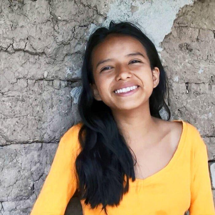 Ecuadorilainen tyttö nojaa hymyillen kiviseen seinään.