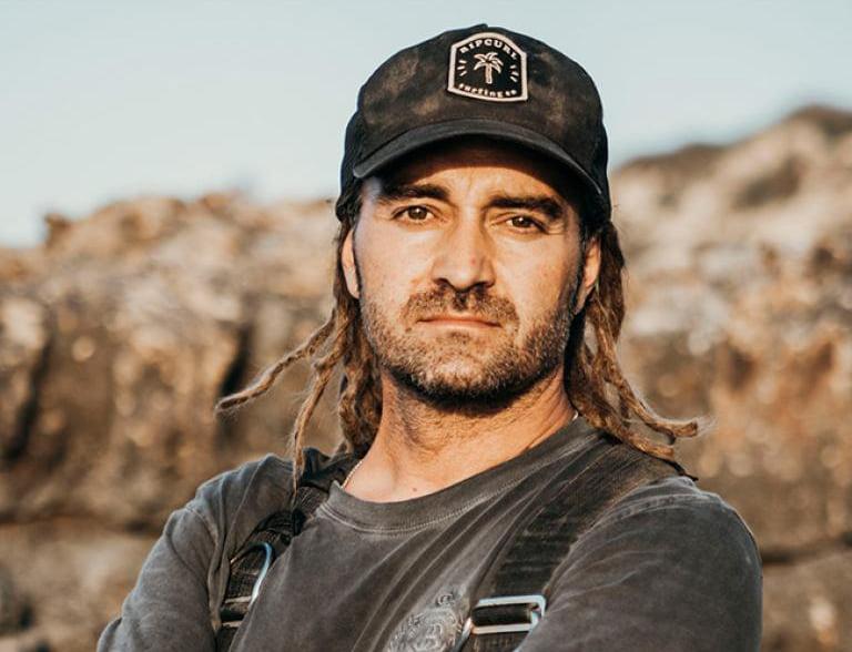Mikko Paasi seisoo lippalakki päässään maiseman edessä ja katsoo kameraan päättäväinen ilme kasvoillaan.