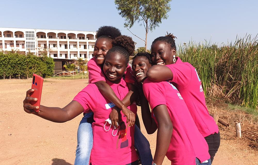 Neljä pinkkeihin paitoihin pukeutunutta nuorta ottaa nauraen selfietä Guinea-Bissaussa.