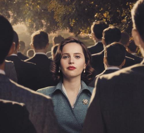 OIkeuden puolesta -elokuvaan liittyvässä kuvassa nainen katsoo vakavana kameraan miesjoukon olkapäiden yli.