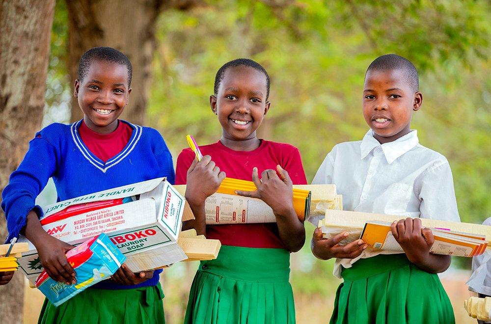 Kolme tansanialaista tyttöä seisoo rinnakkain ja pitelee Planin jakamia hygieniatarvikkeita.