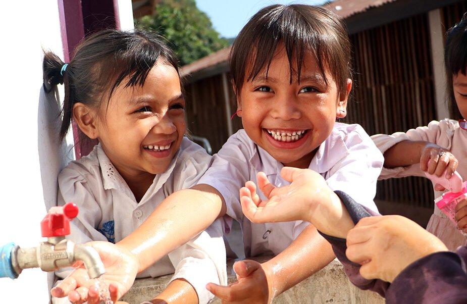 Nauravia tyttöjä pesemässä yhdessä käsiään Laosissa.