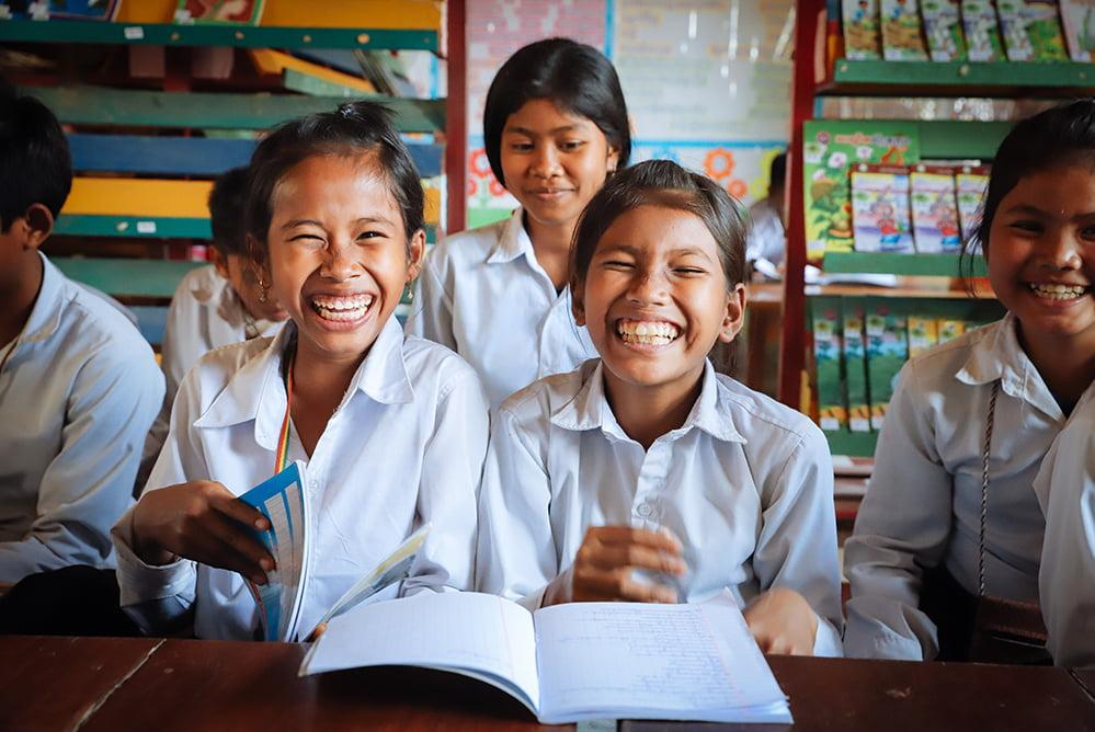 Kambodzalaiset tytöt nauravat koululuokassa.