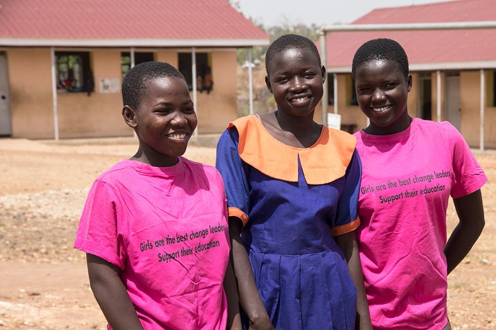 Kolme ugandalaista tyttöä seisoo hymyillen aurinkoisella pihalla.