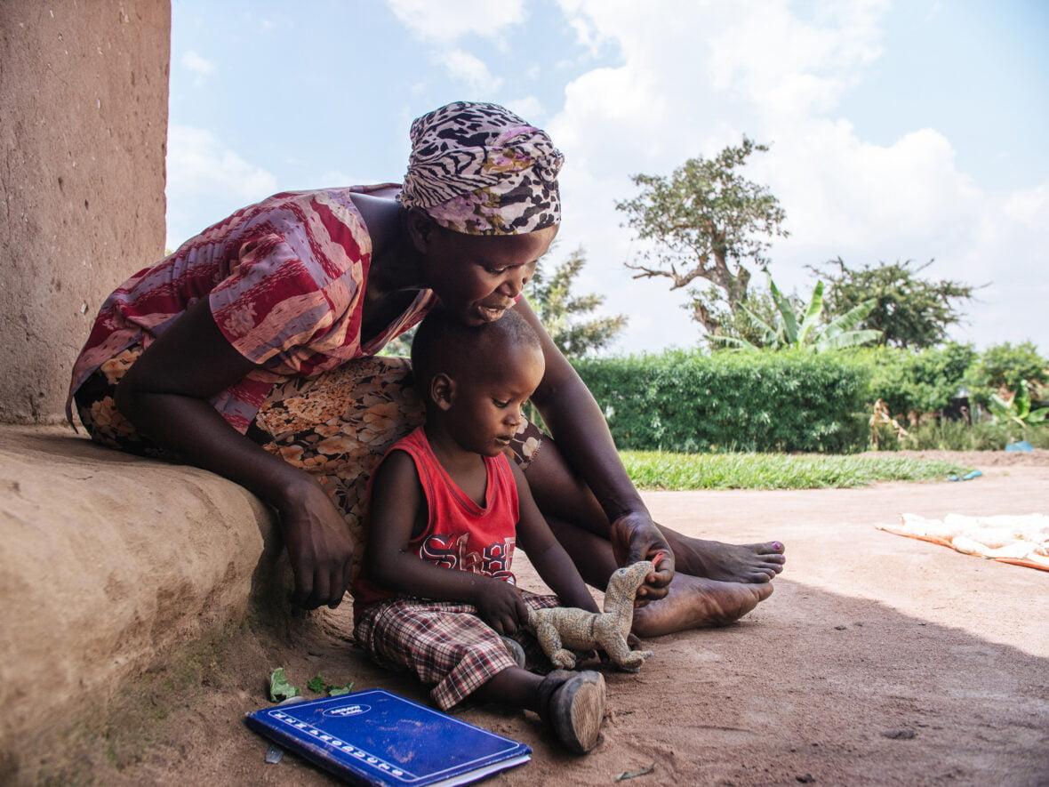 Äiti istuu rappusilla pihalla ja leikkii poikansa kanssa Ugandassa