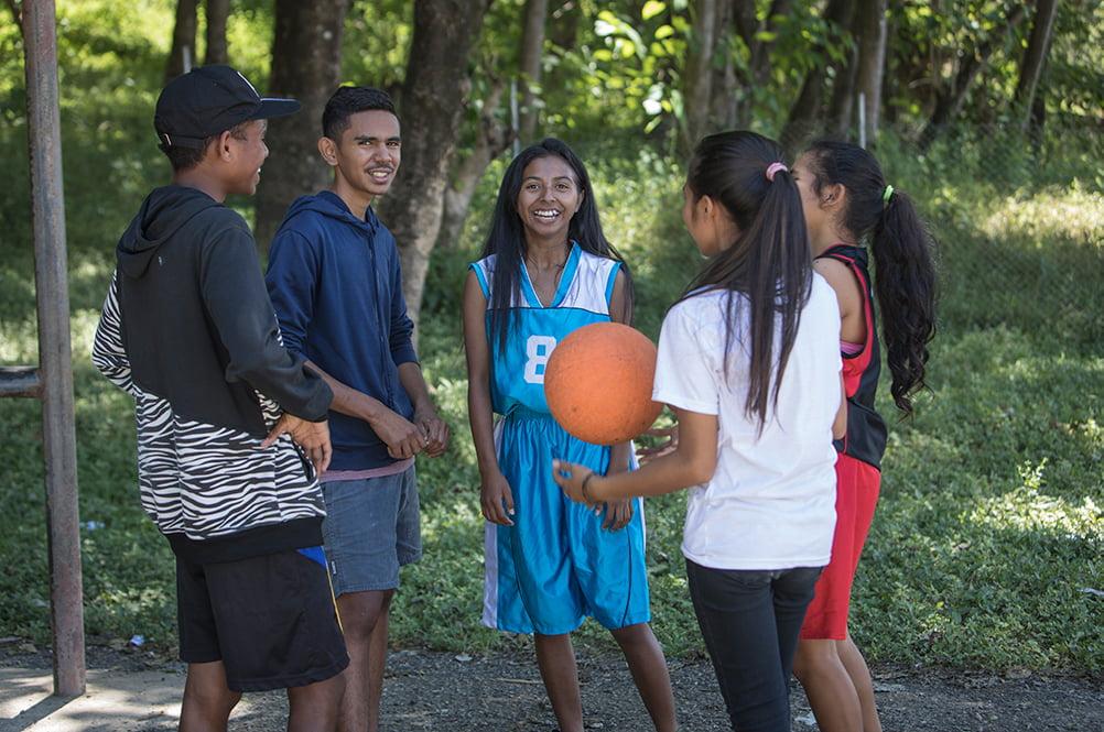 Viisi itätimorilaista nuorta seisoo ringissä kentän reunalla. Yksi nuorista heittelee käsissään koripalloa.