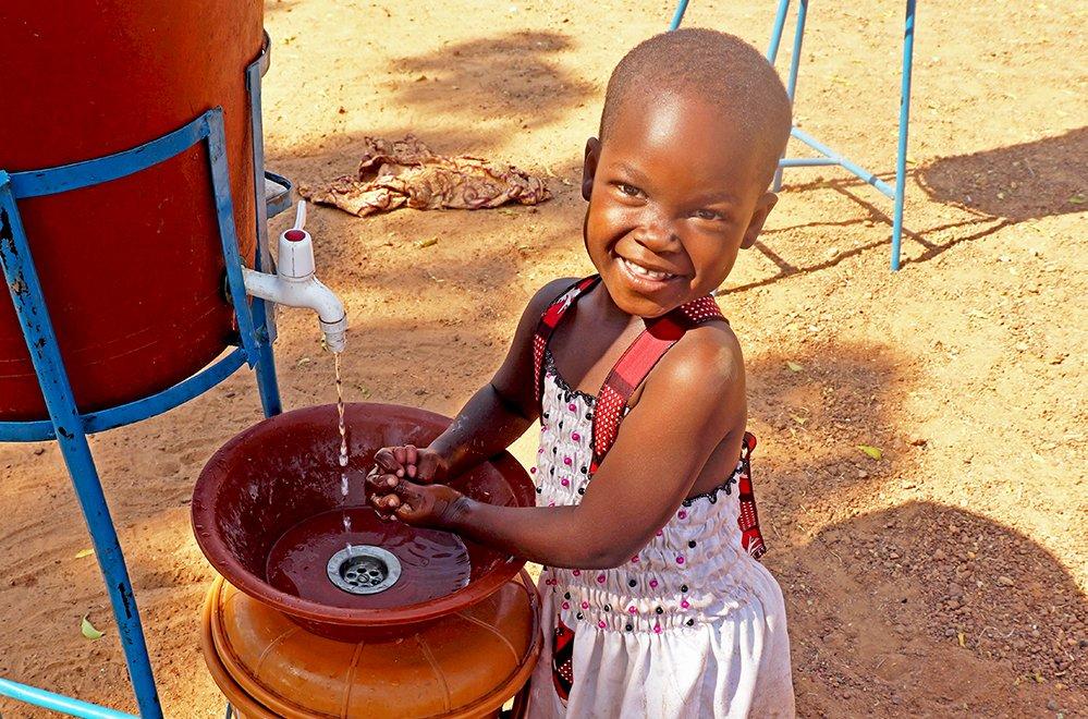 Pieni tyttö pesee käsiään Burkina Fasossa.