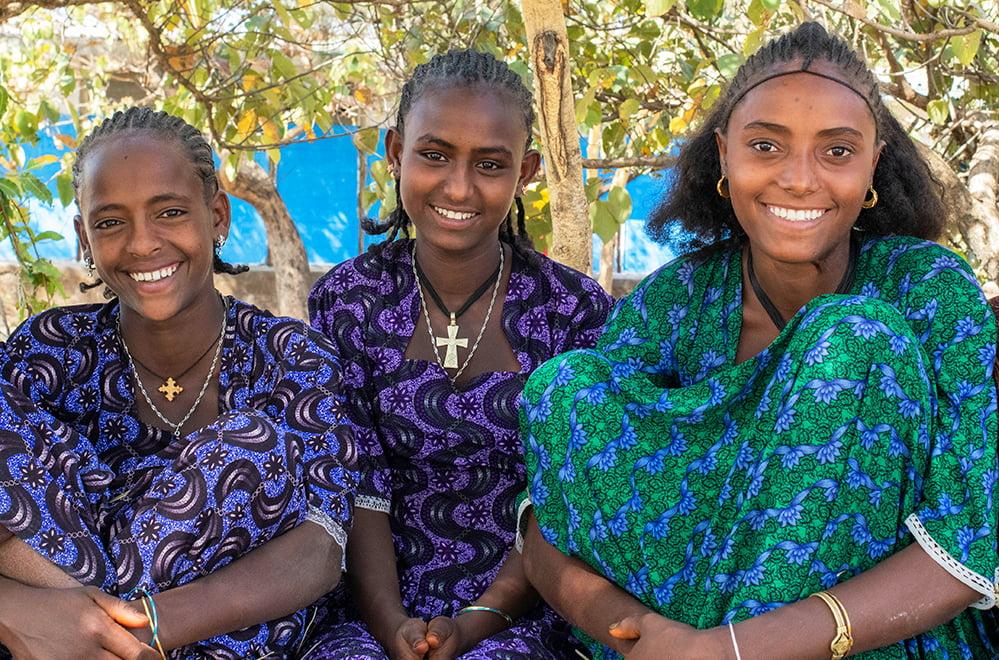 Kolme hymyilevää etiopialaista tyttöä istuu lähekkäin puiden alla.