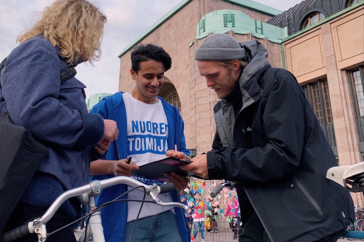 Nuoret toimijat -paitainen nuori pyytää kahta ohikulkijaa allekirjoittamaan vetoomusta kadulla.