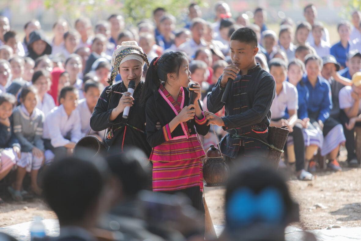 Kolme laosilaisnuorta esittää näytelmää koulun pihalla isolle koululaisyleisölle.