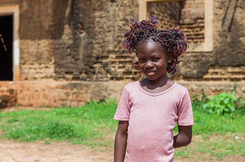 Tyttö seisoo aukiolla vaaleanpunaisessa paidassa ja virnistää kameralle.