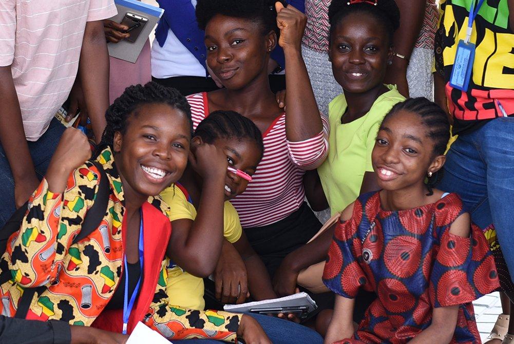 Ryhmä tyttöjä poseeraa hymyillen kameralle.