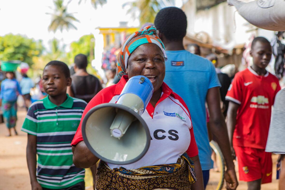 Mosambikilaisnainen huutaa megafoniin väkijoukossa.