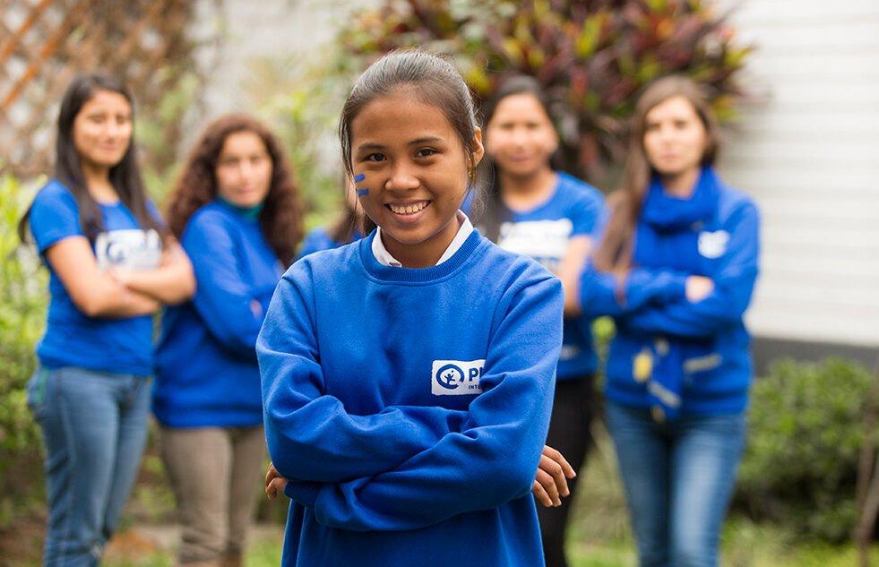 Planin paitaan pukeutunut perulainen tyttö katsoo kameraan hymyillen. Taustalla seisoo neljä tyttöä lisää. Kaikilla tytöillä on kädet puuskassa.