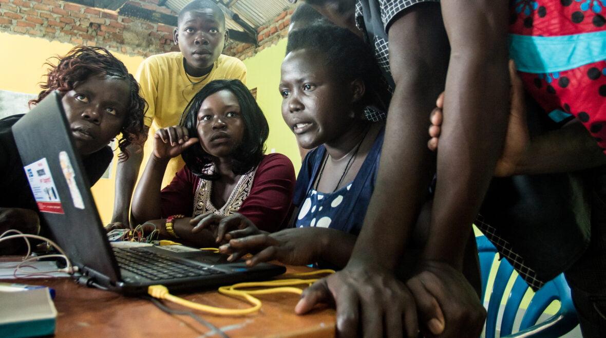 Nuoria tietokonetta käyttämässä Ugandassa.