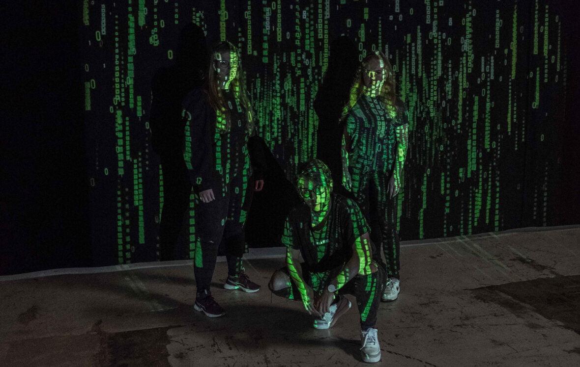 Kolme nuorta poseeraa, heihin on heijastettu projektorilla mustavihreää digitalista kuvaa.