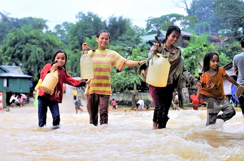 Kaksi naista ja kaksi tyttöä kävelevät vesikanistereiden kanssa tulvivassa vedessä.
