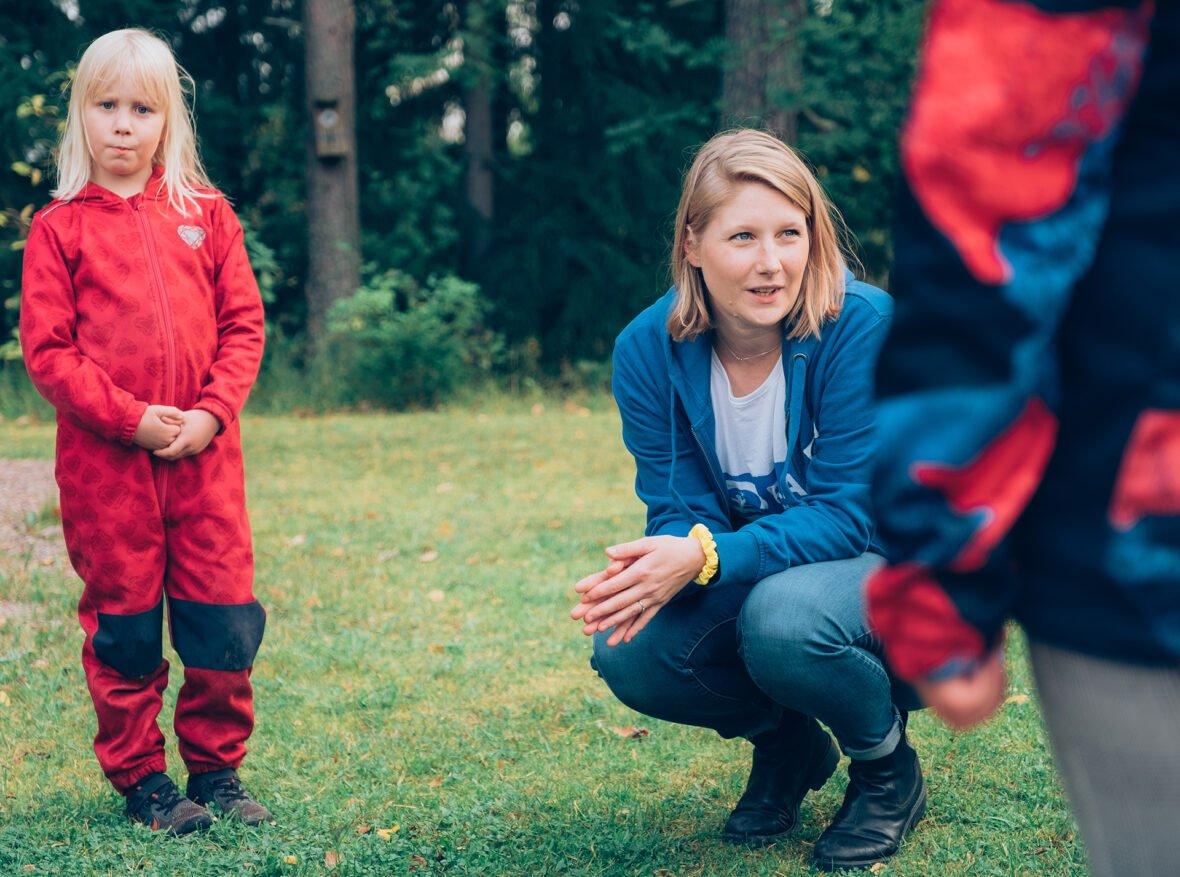 Lapsen oikeuksien lähettiläs juttelee lasten kanssa ulkona.