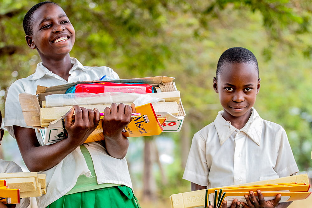 Kaksi tansanialaista tyttöä hymyilee ja kantaa sylissään tarvikkeita.