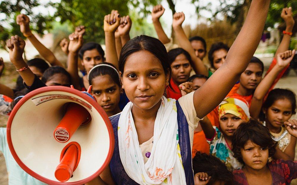 Joukko intialaisia tyttöjä on nostanut kätensä ilmaan. Yhdellä tytöistä on megafoni kädessään.