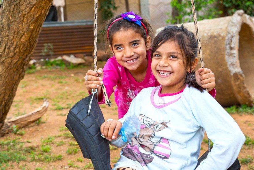 Kaksi paraguaylaista tyttöä istuu yhdessä keinussa.