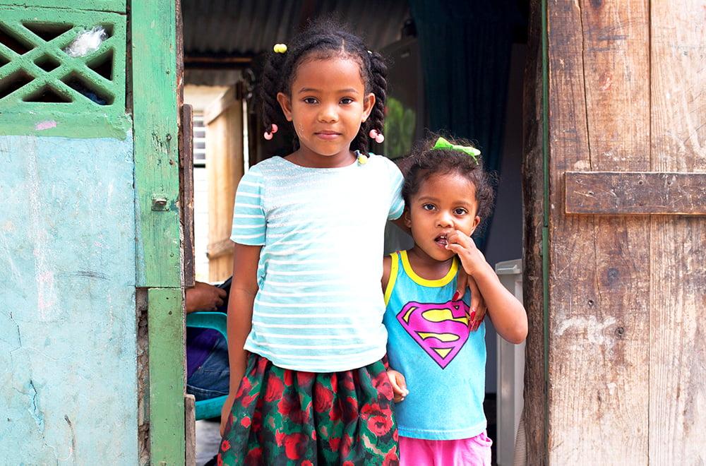 Kaksi pientä tyttöä seisoo lähekkäin kotinsa ovella Dominikaanisessa tasavallassa.