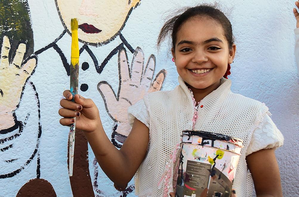 Tyttö seisoo pensseli ja maalipurkki kädessään värikkään seinän edessä.