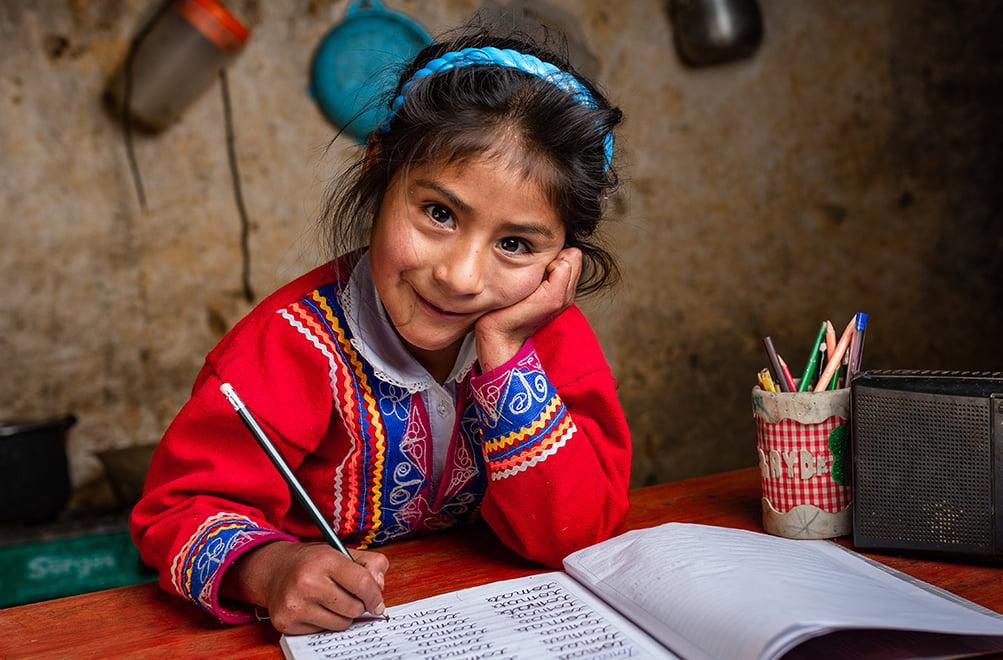 Perulainen tyttö istuu pöydän ääressä tekemässä koulutehtäviä.