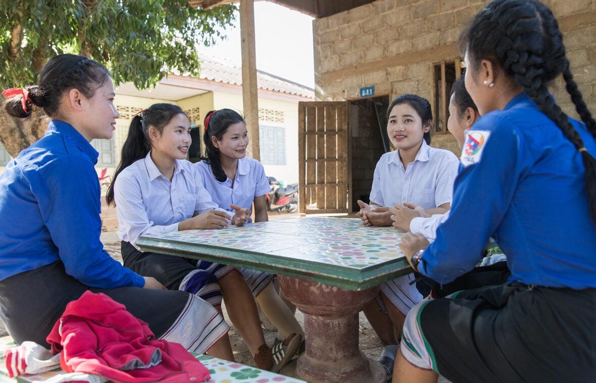 Teini-ikäisiä tyttöjä koulun pihalla Laosissa