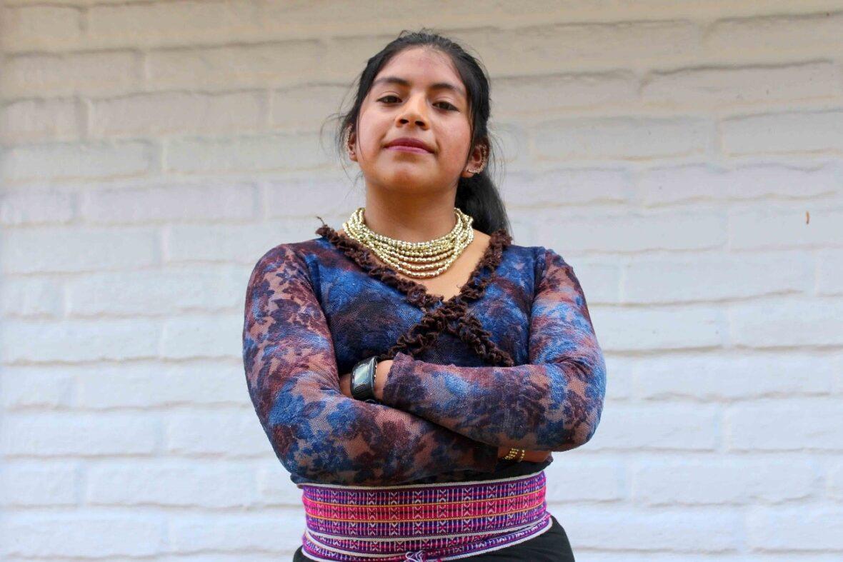 Ecuadorilainen tyttö poseera kameralle kädet puuskassa.