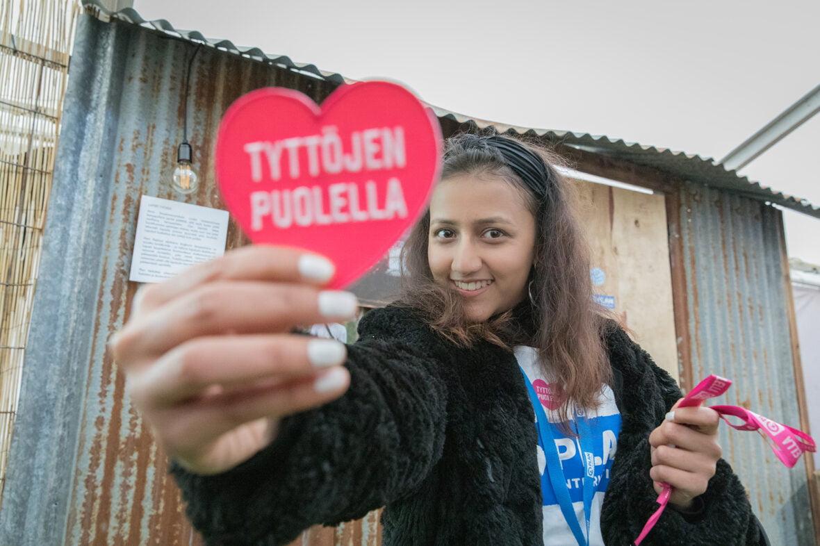 """Planin nuori vapaaehtoinen hymyilee ja näyttää kameralla sydämenmuotoista """"tyttöjen puolella"""" -tarraa."""