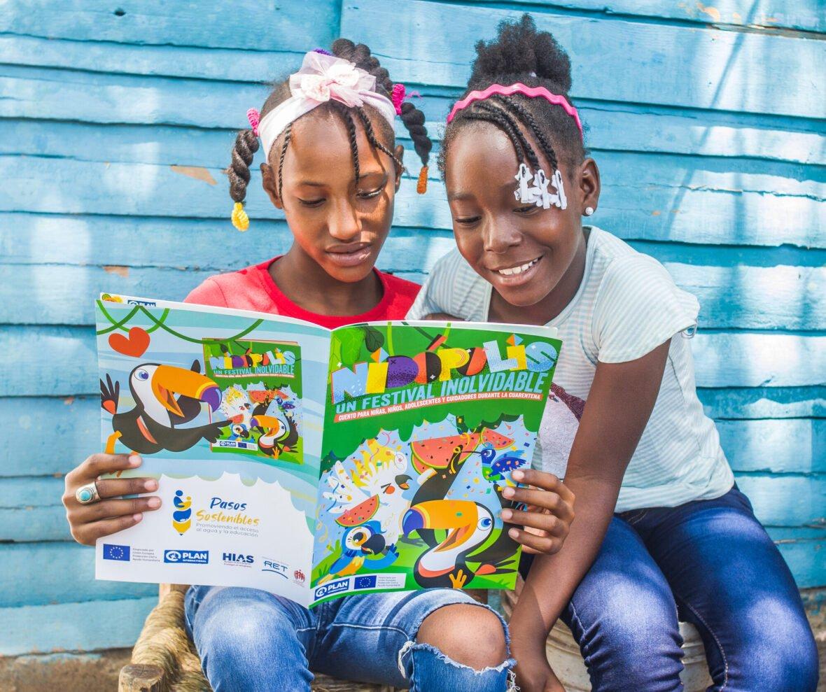 Kaksi kolumbialaista tyttöä lukee lasten lehteä ja hymyilee.
