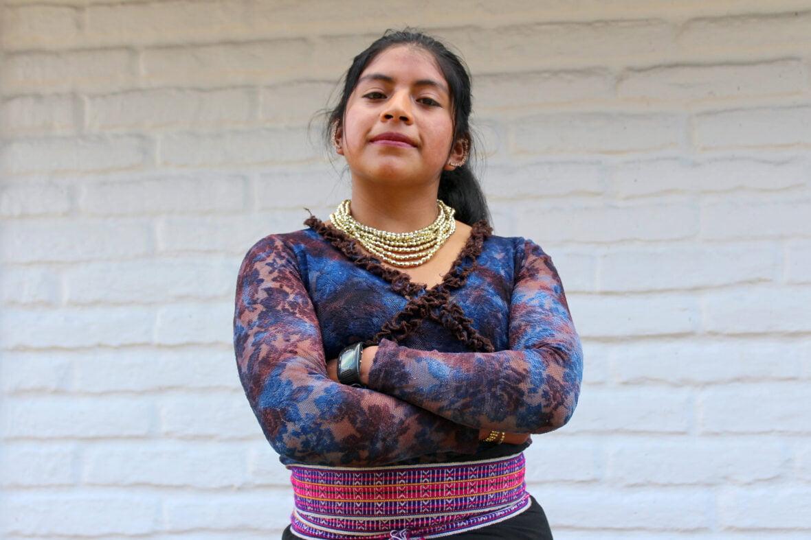 Ecuadorilainen Yadira kädet puuskassa tiiliseinän edessä.